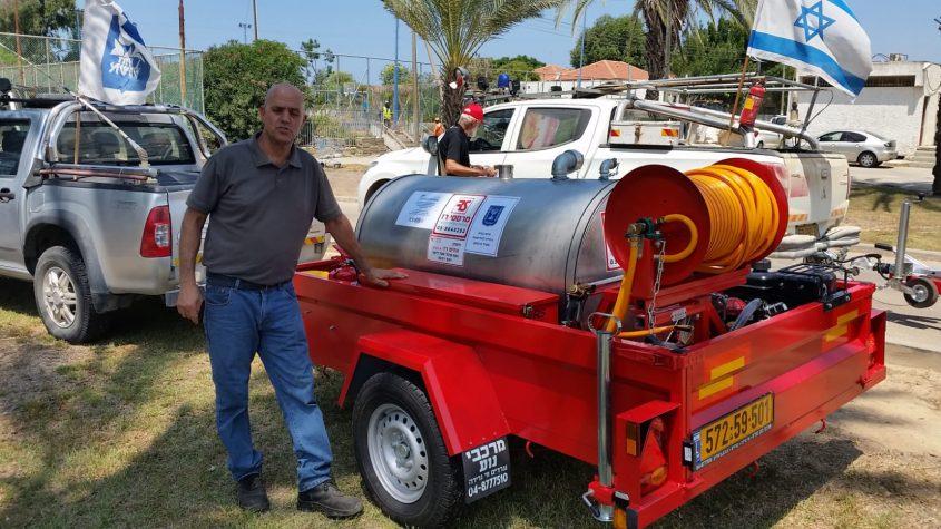 שמוליק רז עם אחד מנגררי הכיבוי שייצר לחוף אשקלון. צילום: יאיר הרוש