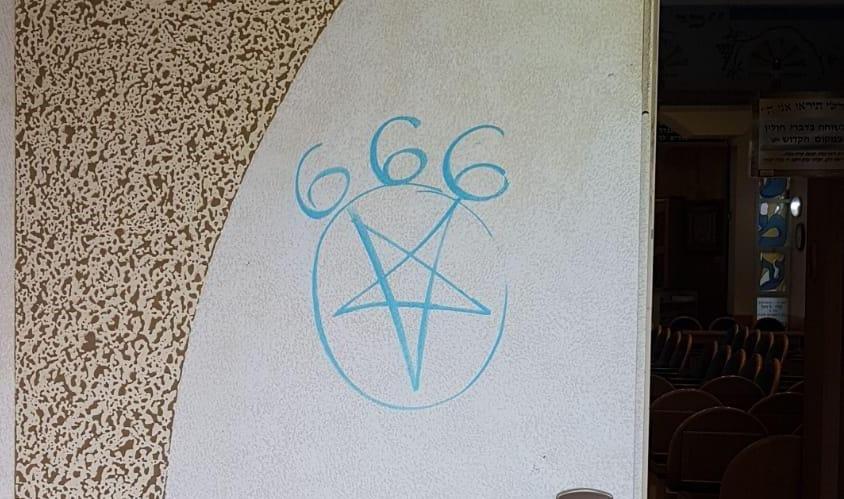 דלת בית הכנסת עם הכתובת עליה. צילום: דוברות המשטרה