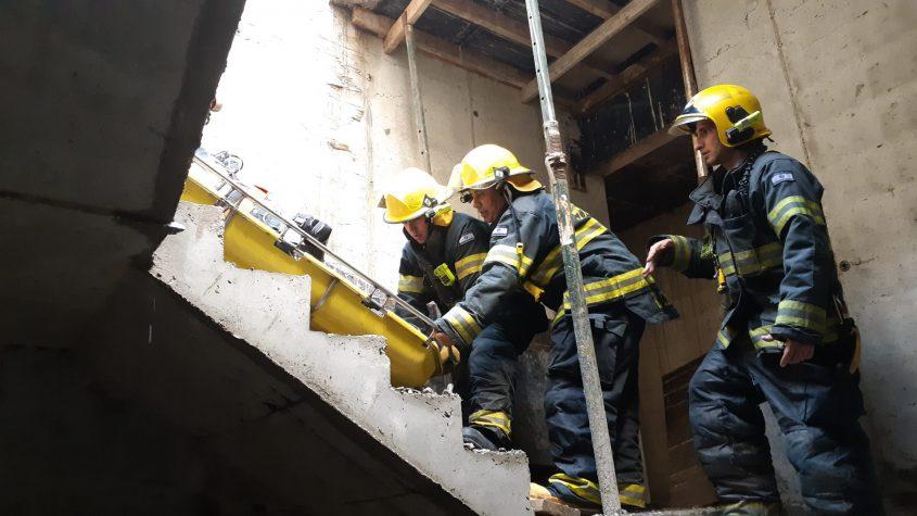 הכבאים מחלצים את הפצוע בחדר המדרגות. צילום: אלירם משה