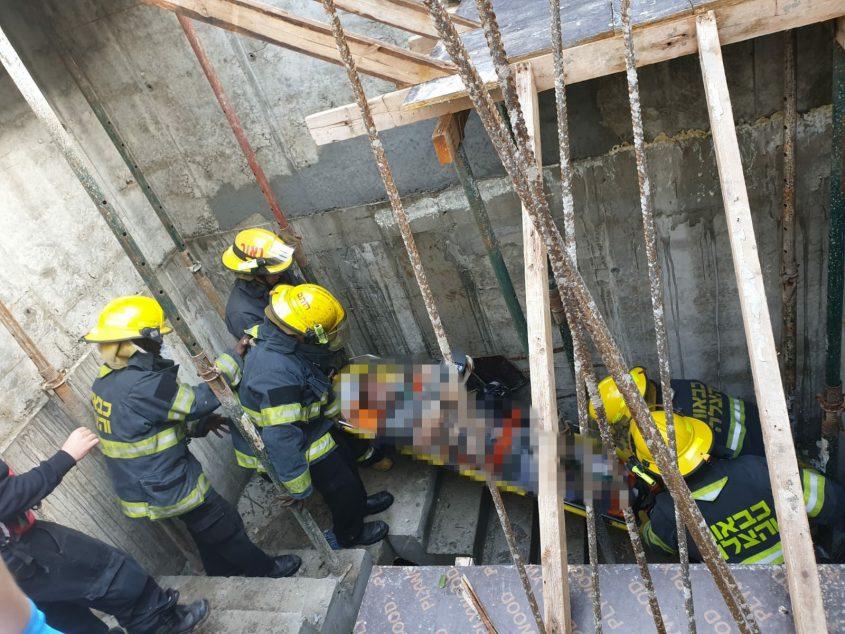 הכבאים מחלצים את הפצוע דרך המדרגות. צילום: רן זמיר