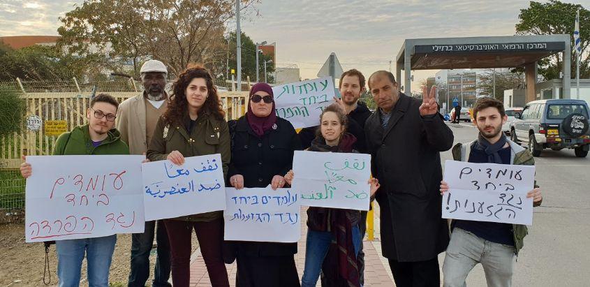 """פעילי """"עומדים ביחד"""" מנושאים שלטים. צילום: עומדים ביחד"""