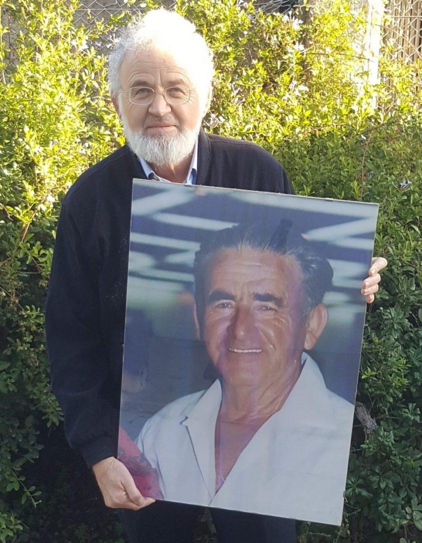 """עו""""ד אלון גורן מחזיק בידו את תמונת אביו עו""""ד יונה גורן"""