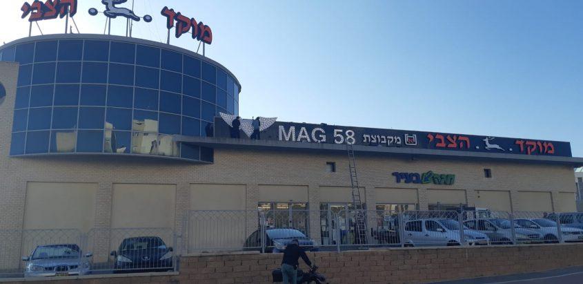 מתקינים את שלטי מאג 58 על חזית מוקד הצבי באשקלון. צילום: אלירם משה