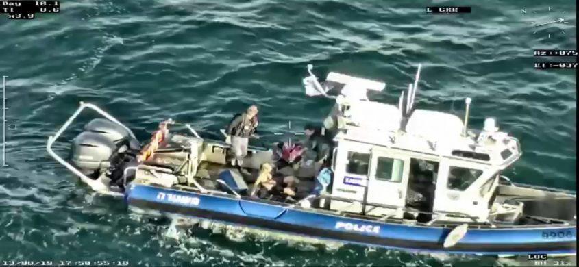 השניים על הסירה של השיטור הימי לאחר החילוץ. צילום: דוברות המשטרה