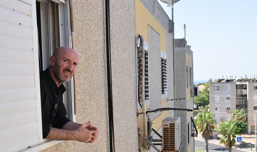 סימון טטרו בחלון הבית בו גדל. צילום: עדי תשובה