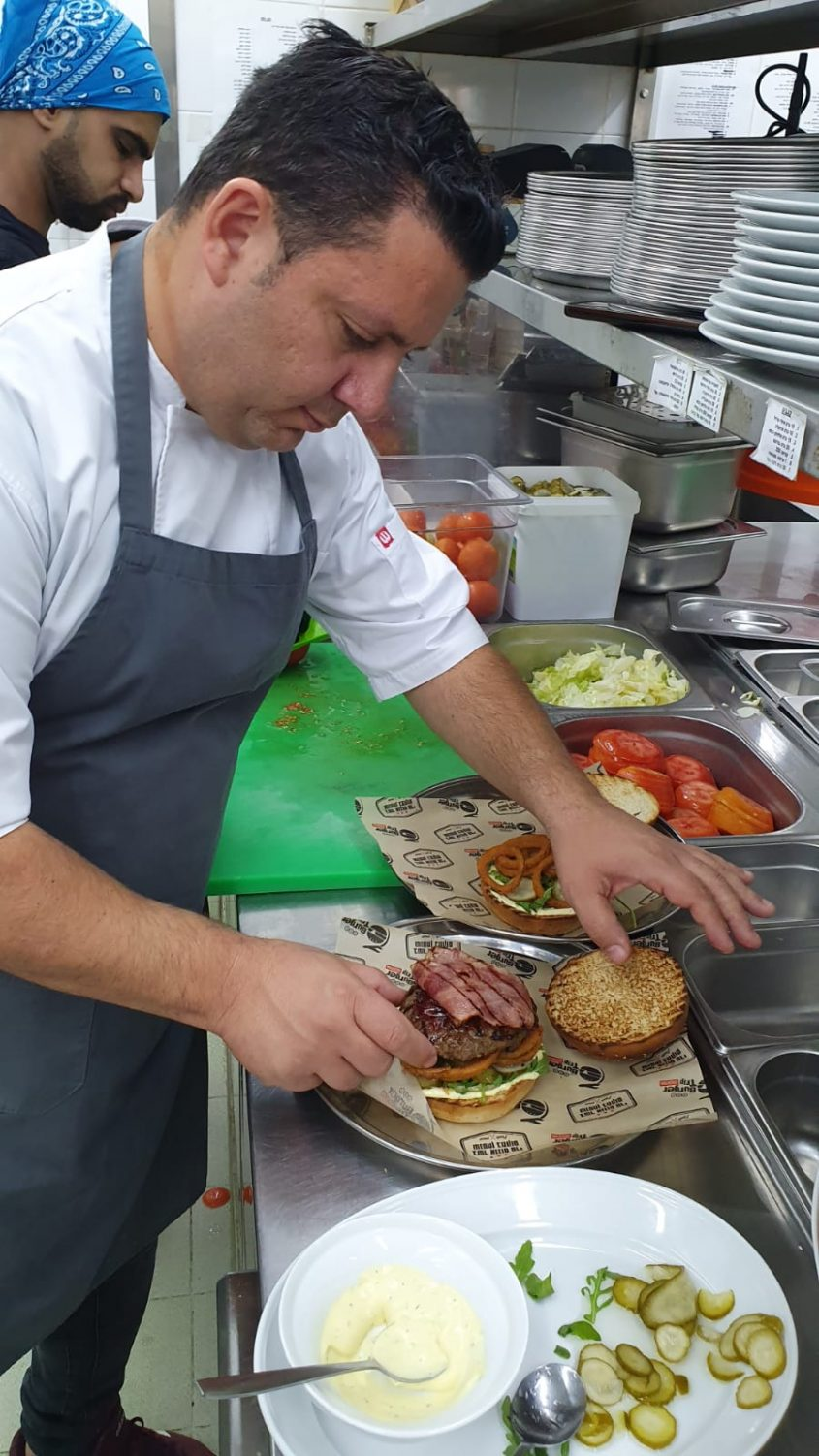 שף מיקי סויסה מכין המבורגר. צילום: עדי תשובה