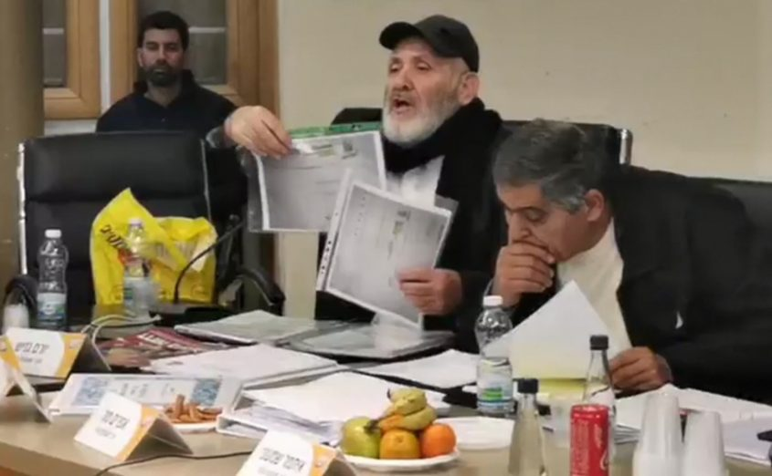 חבר המועצה רמי סופר מציג את המסמכים בישיבת המועצה