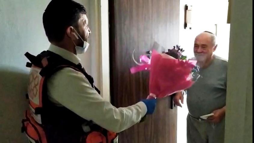 הרב שמעון לוגסי מעניק פרחים לניצול שואה