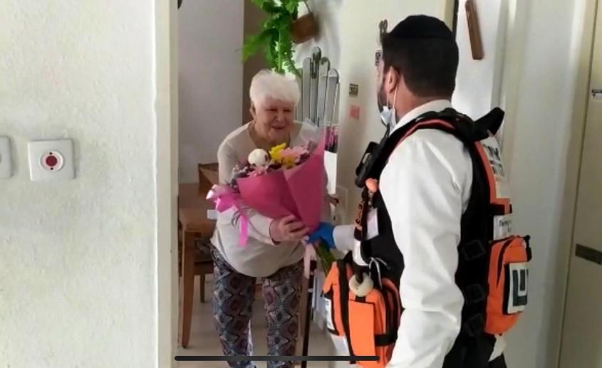 הרב שמעון לוגסי מעניק פרחים לניצולת שואה