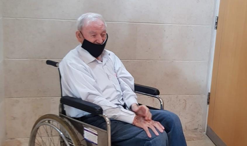 אבי ויינראוך בכיסא גלגלים בפתח אולם הדיונים השבוע