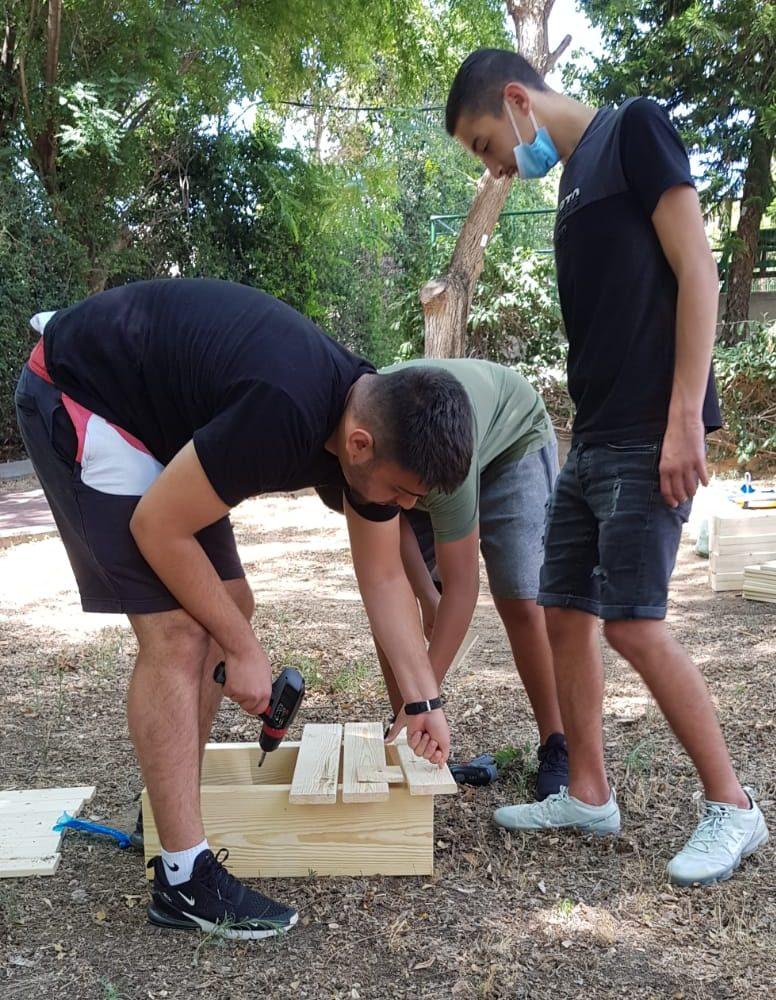 התלמידים בונים שולחנות וספסלים מעץ