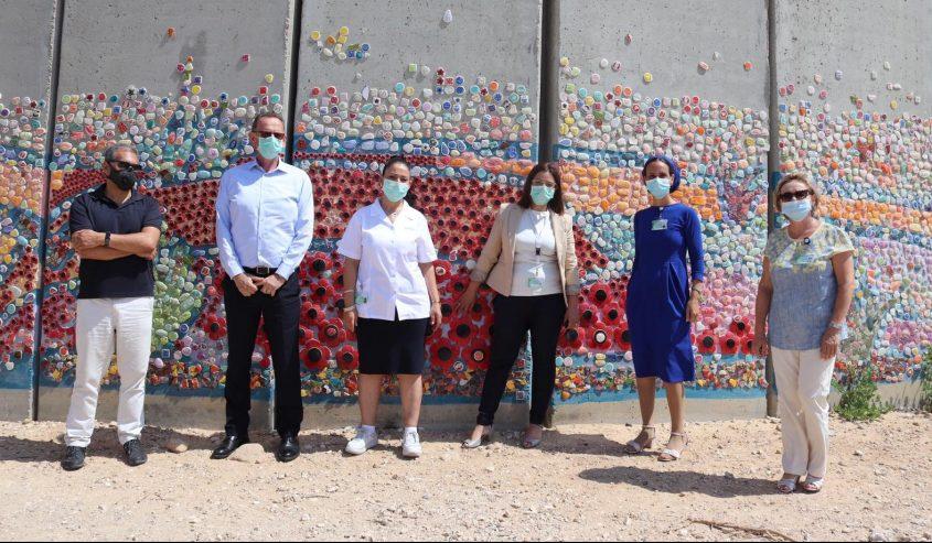 לוקר ונציגי מחוז הדרום בשירותי בריאות כללית ליד החומה בנתיב העשרה. צילום: דוברות הכללית