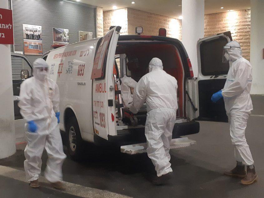 """צוות מד""""א מוציא חולה קורונה בכניסה לחדר המיון בבית החולים ברזילי. צילום: אלירם משה"""