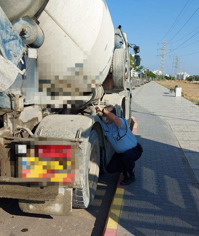 שוטר בוחן רכב בודק את את תקינות צמיגיה של משאית שנתפסה. צילום: דוברות המשטרה