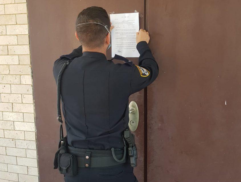 שוטר תולה צו מנהלי על דלתות בית הכנסת. צילום: דוברות המשטרה