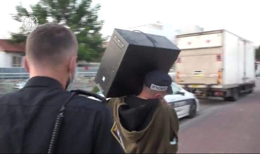 השוטרים שביצעו את המעצר לוקחים מחשב שאיתו בוצעו ההתכתבויות מביתו של אחד החשודים. צילום: דוברות המשטרה