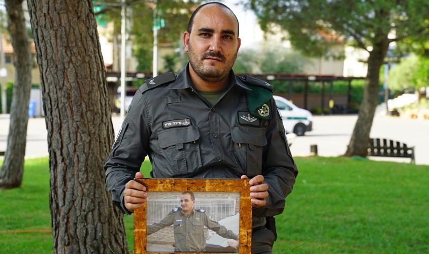 """מיכה פרץ עם תמונתו של רונן אחיו ז""""ל. צילום: דוברות המשטרה"""