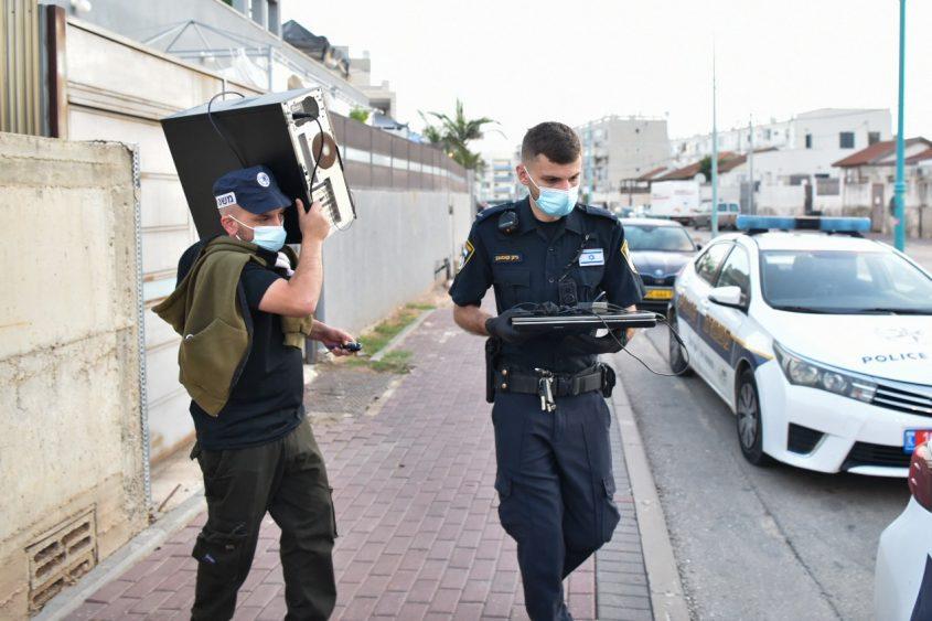 שוטרים יוצאים לביתו של אחד החשודים עם המחשב שאיתו על פי החשד התכתב. צילום: דוברות המשטרה