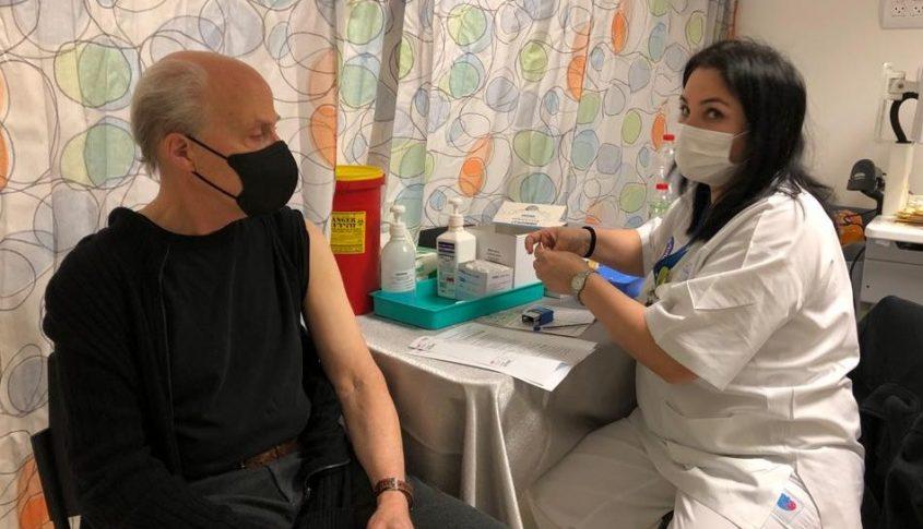 פרופ' רוג'ר דויד קורנברג מקבל את מנת החיסון הראשונה לקורונה, במרפאת חיסוני הקורונה של המרכז הרפואי ברזילי. צילום: דוברות ברזילי