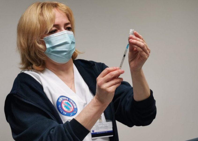 אחות במרכז הרפואי ברזילי שואבת את נוזל החיסון לקורונה מהאמפולה למזרק. צילום: דוד לוי