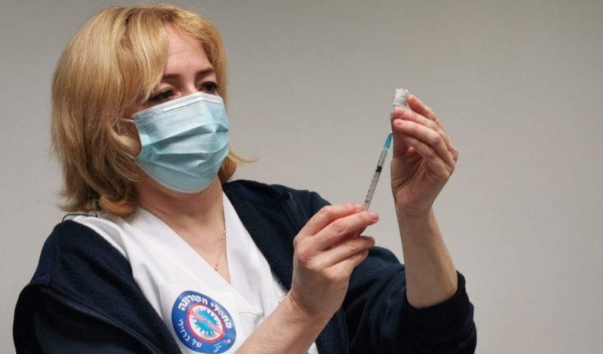 אחות במרכז הרפואי ברזילי מחזיקה את החיסון לקורונה