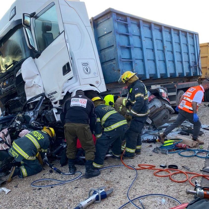 """לוחמי האש עומלים לחלץ את המכונית מתחת למשאית הפולטריילר תאונה הקטלנית בכביש 334. צילום: דוברות כב""""ה דרום"""