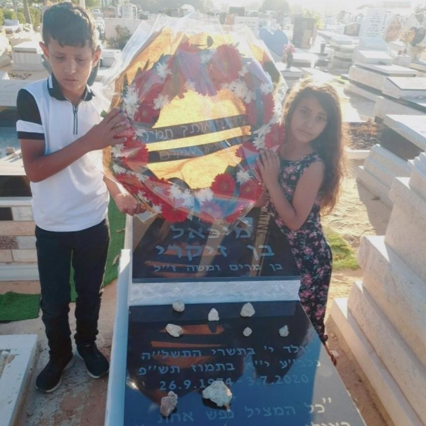 """ילדי משפחת אלקרים מניחים זר בקבר של מיכאל בן זיקרי ז""""ל"""