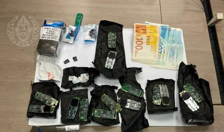 """הכסף וחלק מהסלולרים שנתפסו. צילום: דוברות שב""""ס"""