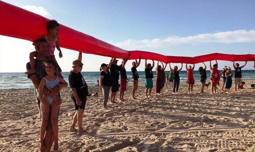 """מיצג מחאה """"הקו האדום"""" בחוף מעין צבי. צילום: דורון גזית"""
